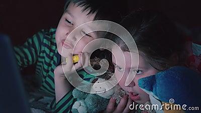 Broer en zuster het letten op video's op laptop die op bed in de avond 4K ligt stock videobeelden