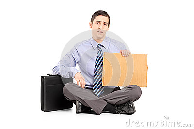 Broke businessman begging with a piece of cardboard