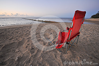Broken chair on beach by ocean during sunrise