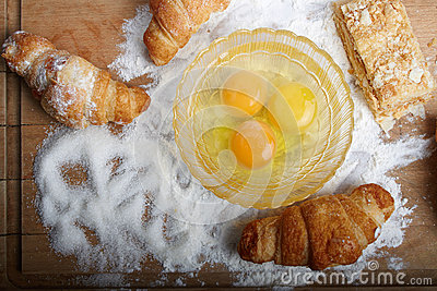 The broken eggs and baking on the wooden board poured by a flour