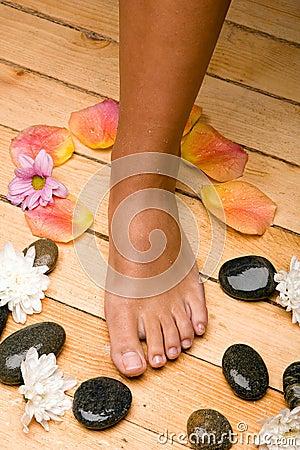 Bronzed foot on board floor