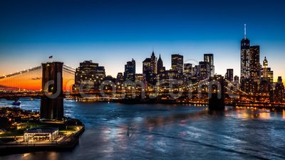 Brooklyn Bridge at sunset. The iconic landmark spans between Brooklyn and the New York Financial District skyline, dominated by the Freedom Tower