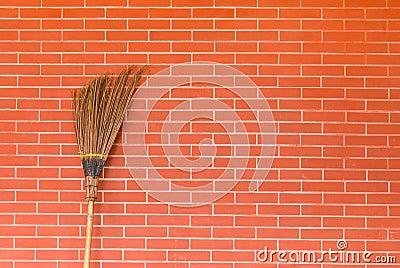 Broom on brick wall