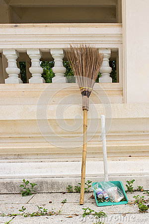 Broom and dust pan lean on wall