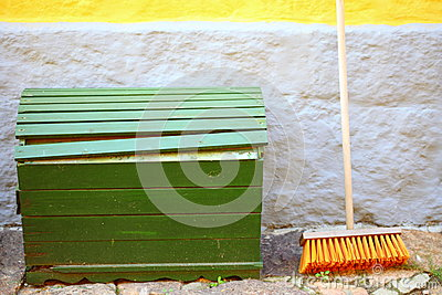 Broom on wall and wooden box outdoor - housework