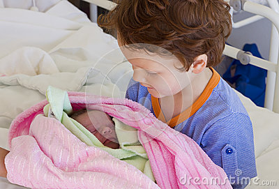 Brother meeting newborn sister