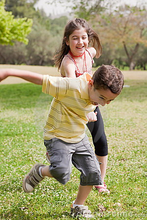 Brother pulling his sister in the park