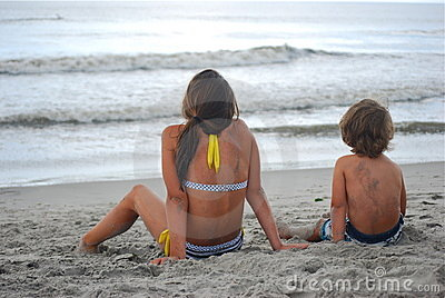 A brother and sister on beach staring at ocean