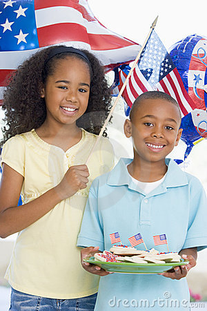 Brother and sister on fourth of July with flags