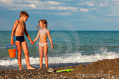 Brother and sister hold hands and stand on beach
