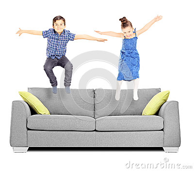 Brother And Sister Jumping On Sofa Stock Photo Image