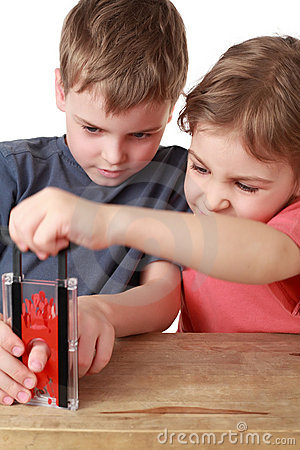 Brother and sister play with little guillotine