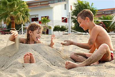 Brother and sister playing in sand on beach