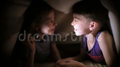Brother and sister read a book under a blanket with a flashlight in brother and sister read a book under a blanket with a flashlight in a dark room at night kids are playing stock footage video of holding sciox Gallery