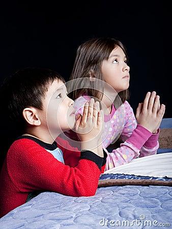 Brother and sister say prayers.