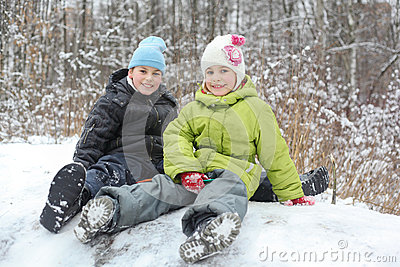 Brother, sister seat on saucer near trees