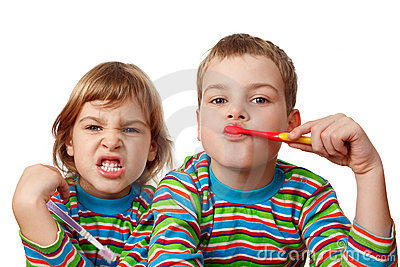 Brother and sister in shirts brush their teeth