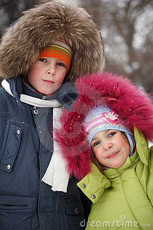 Brother and sister smiling in winter forest