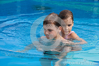 Brother sister swim play in pool