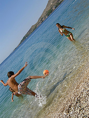 Brother and sisters playing football in the sea