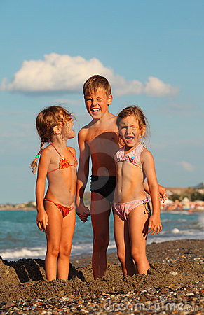 Brother and two sisters are standing on beach
