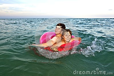 Brothers in a swim ring have fun in the ocean