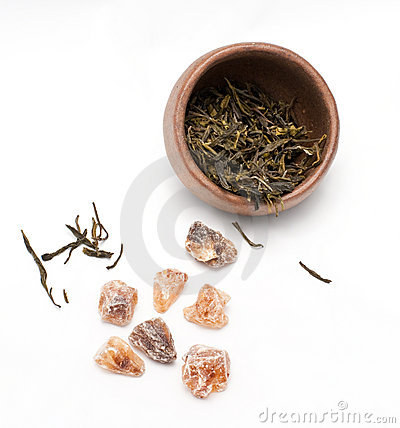 Brown crystal sugar and a tea cup with green tea