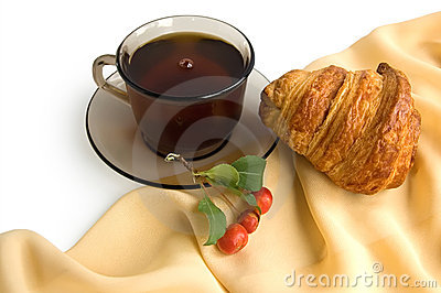 Brown cup of tea and croissants