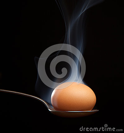 Brown egg wrapped in smoke in spoon