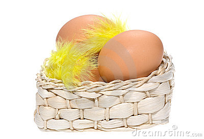Brown eggs with feathers in basket