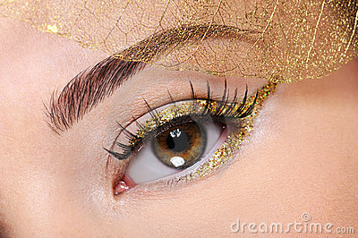 Brown female eye with a glamour golden make-up