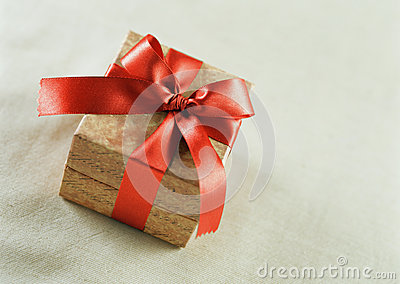 A brown gift with a red satin ribbon and a bow