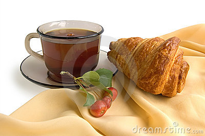 Brown glass cup with tea and croissants