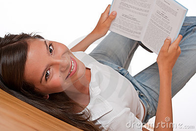 Brown hair teenager lying down holding book