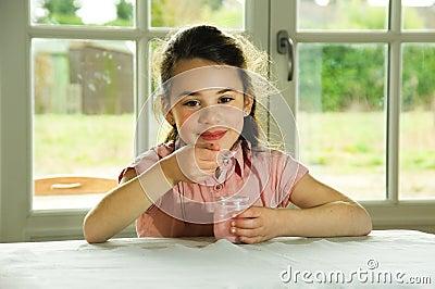 Brown haired child eating yogurt