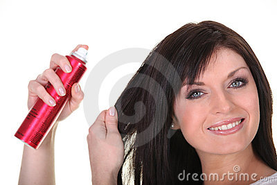Brown-haired woman spraying her hair