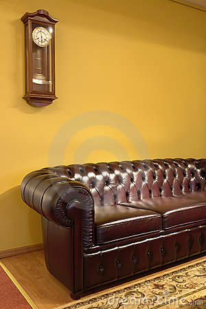 Brown leather sofa and clock