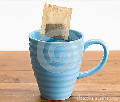 Brown organic green tea bag lowered in mug