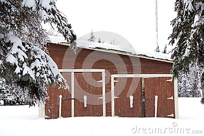 A brown shed in the snow