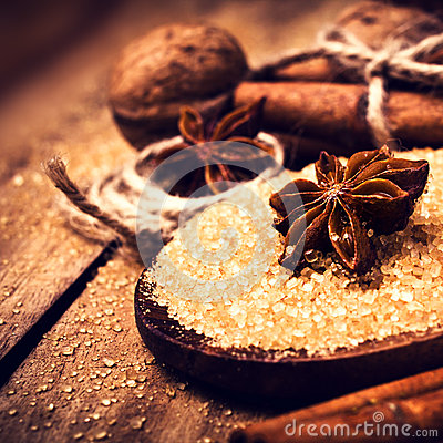 Brown sugar, spices, cinnamon, star anise and nuts on a wooden b