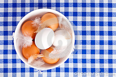 Brown and white eggs, feathers in a bowl