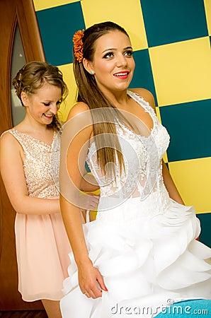 Brud som sätter på bröllopsklänningen