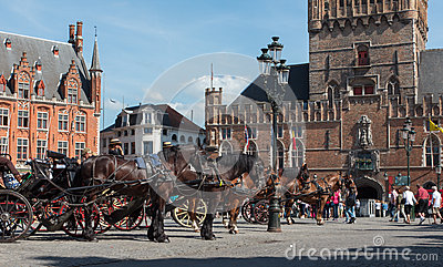 Bruges - The Carriage on the Grote Markt and Belfort van Brugge in background. Editorial Stock Image