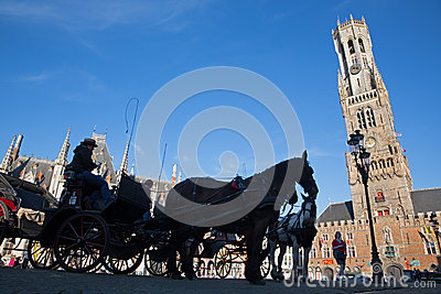 Bruges - The Carriage on the Grote Markt and Belfort van Brugge in background. Editorial Photo