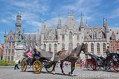 Bruges - The Carriage on the Grote Markt and the Provinciaal Hof building in background. Editorial Photo