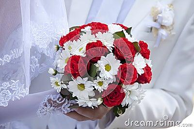 Bruid die het mooie rode boeket van het rozenhuwelijk houdt