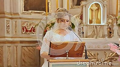 Bruid die in kerk bij haar huwelijk het evangelie lezen Gods` s woord stock videobeelden