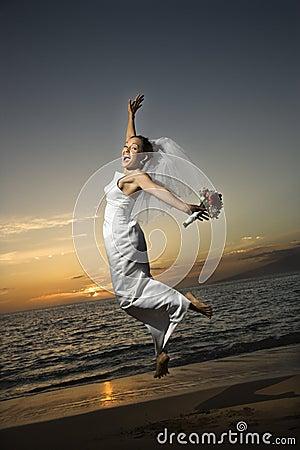 Bruid die op strand springt.