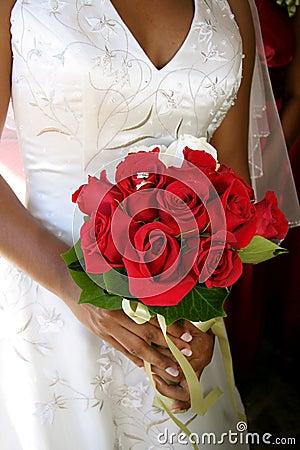 Bruid met trouwringen in rood boeket