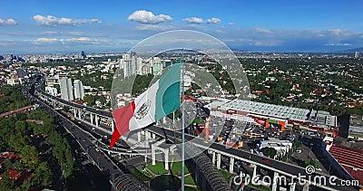 Brummenvogelperspektive eines enormen Wellenartig bewegens der mexikanischen Flagge In der Rückseite Panoramablick von Mexiko Cit stock video